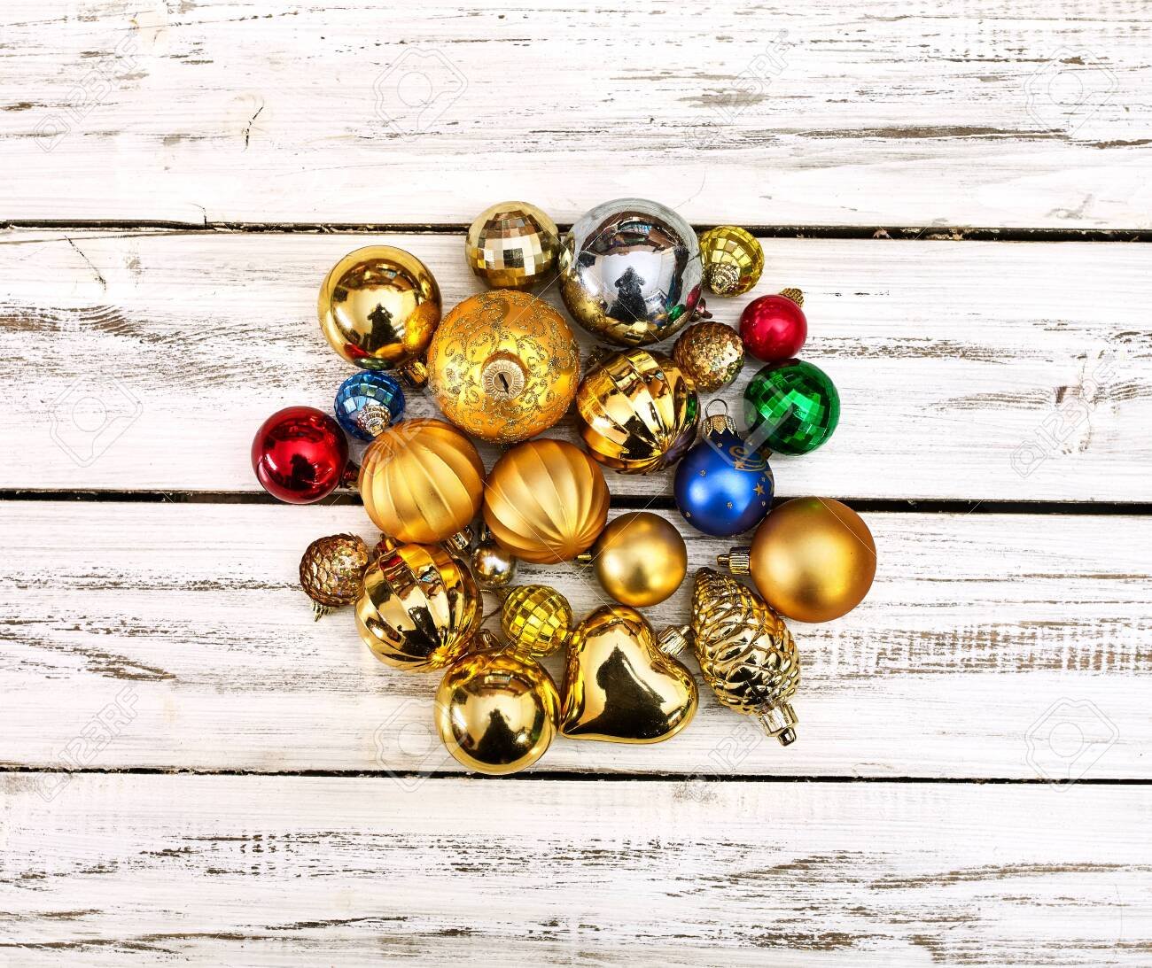 Christmas stack of Xmas balls decorations on white wooden boards on square frame with copy space around still life . - 133940082