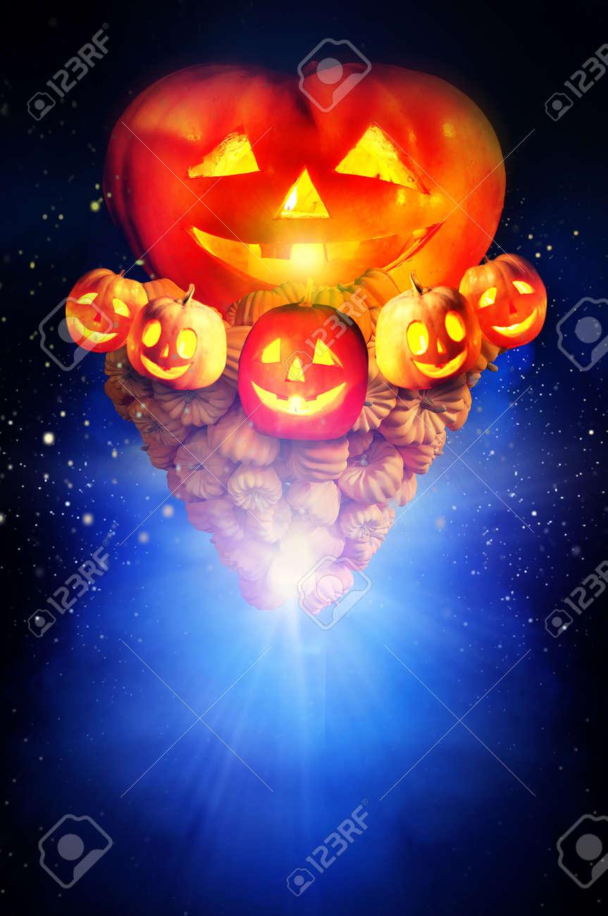 Halloween pumpkin in dark night sky. Concept of jack-o-lantern pumkin tornado up in bright star burst background. - 155787674
