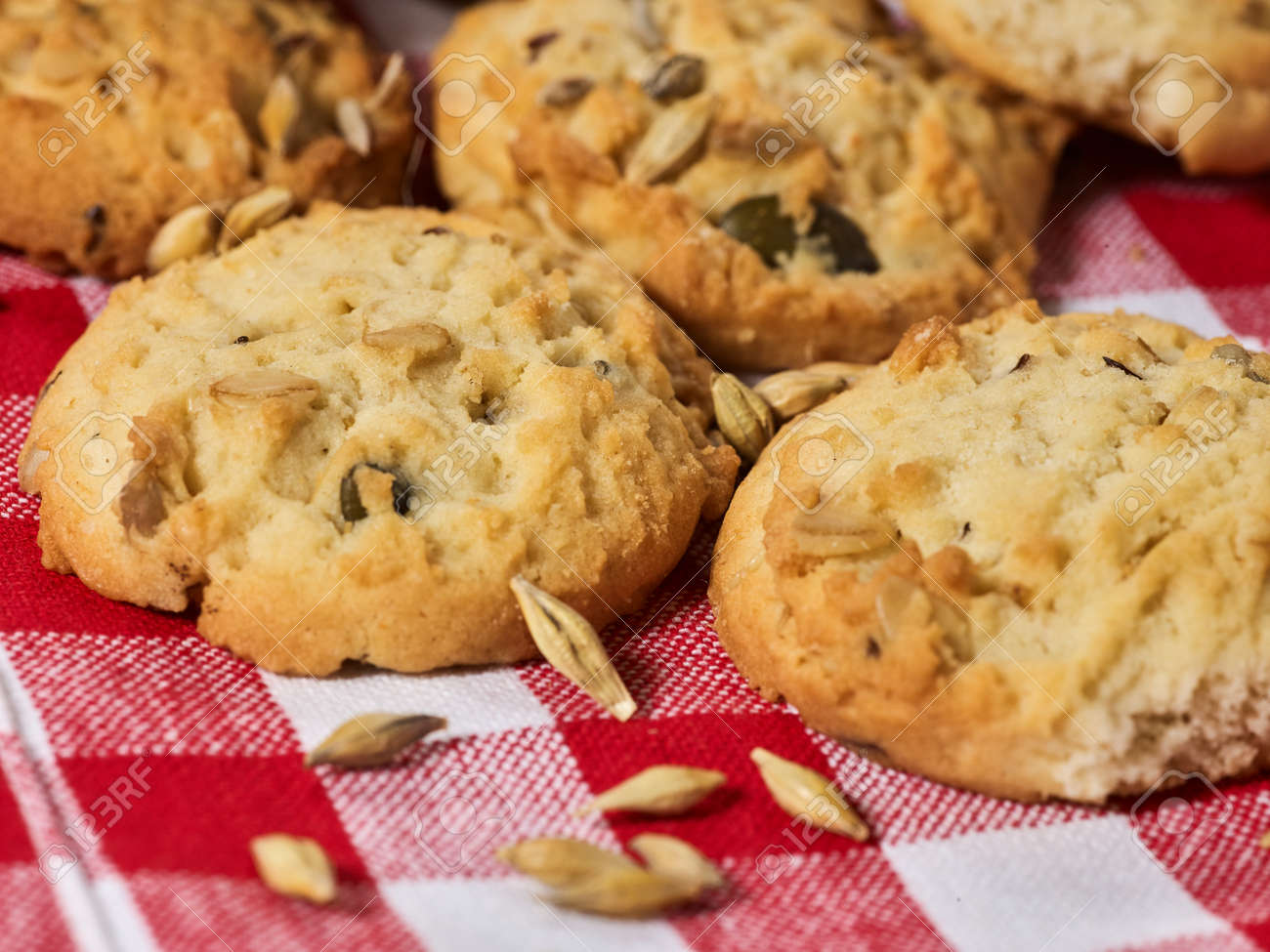 Oatmeal cookies with husk whole oats on red kitchen gingham checkered cotton fabric on table in farm-style. - 156541267
