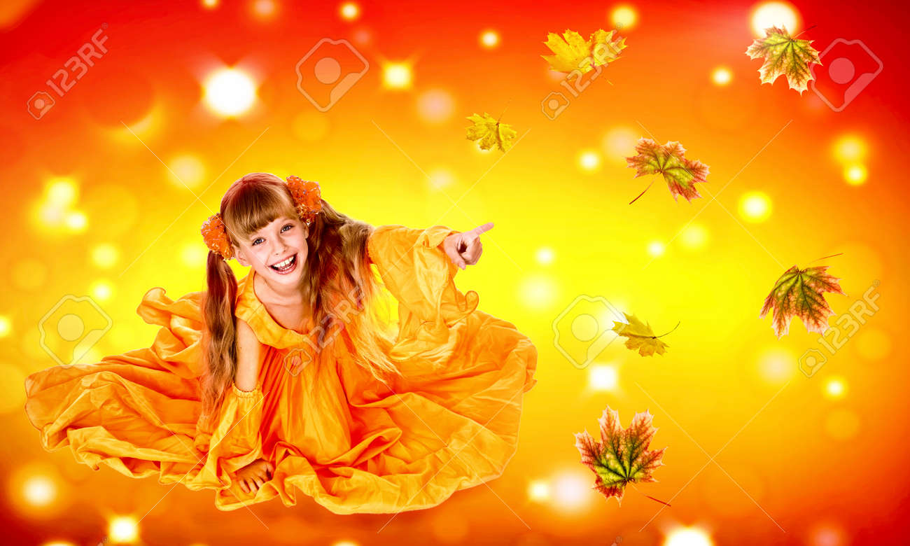 Autumn leaves background with child girl. Conceptual fashion dream in red fall color of september sun. Kid playing with leaves in fall. - 157021051
