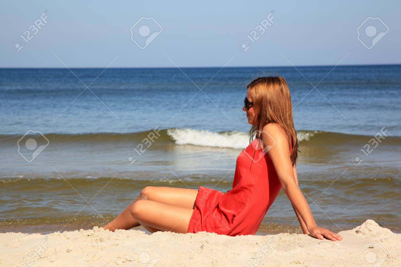 Young woman sitting on a sunny beach Stock Photo - 10568928