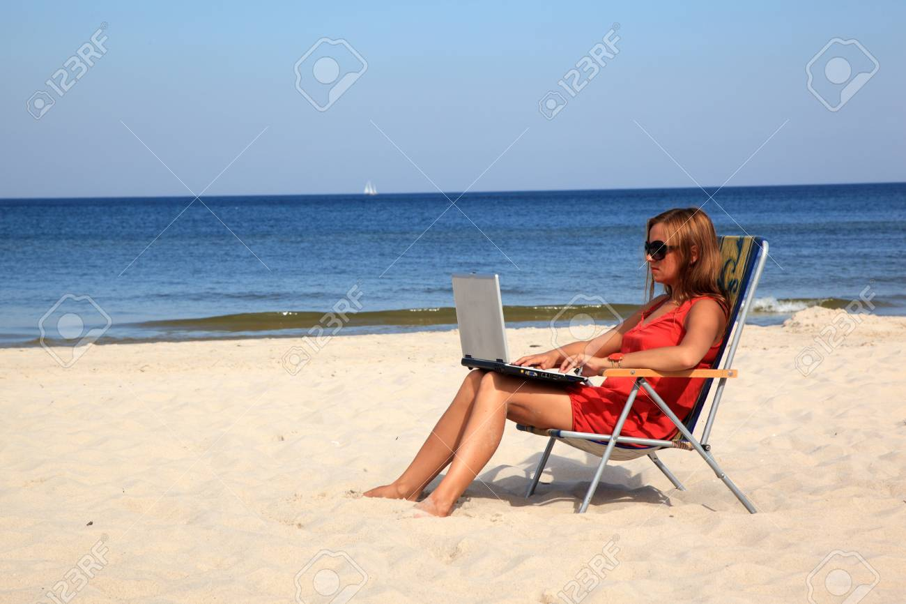 Young woman with laptop is sitting on the sunny beach. Stock Photo - 10568931