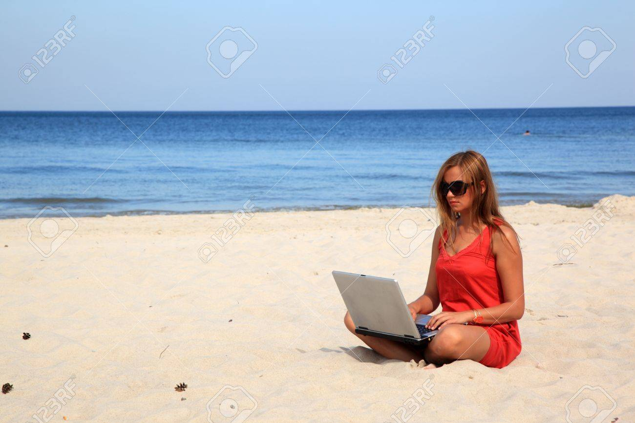 Young woman with laptop is sitting on the sunny beach. Stock Photo - 10568919