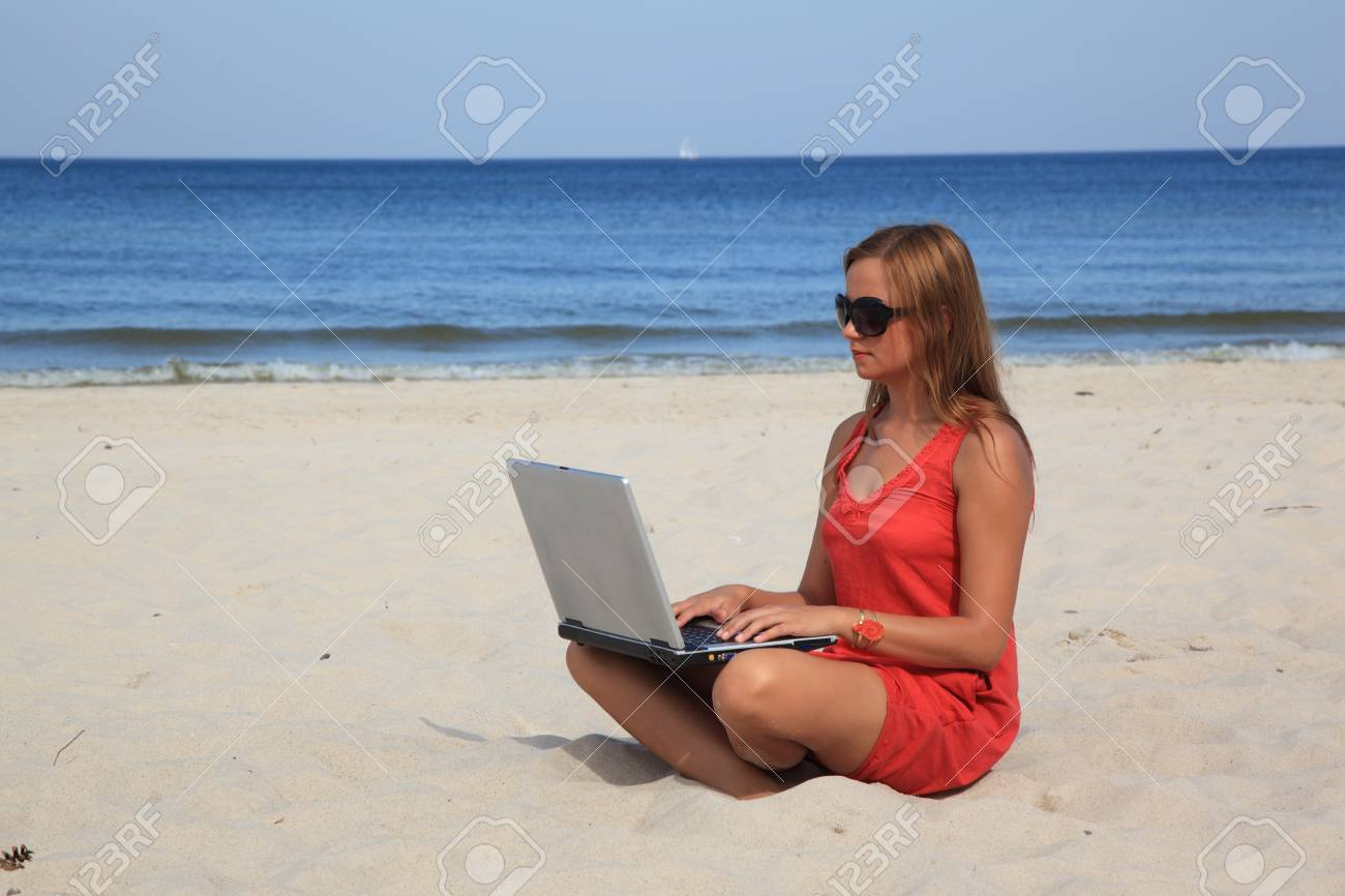 c4bd7bbc9b21 Young woman with laptop is sitting on the sunny beach.
