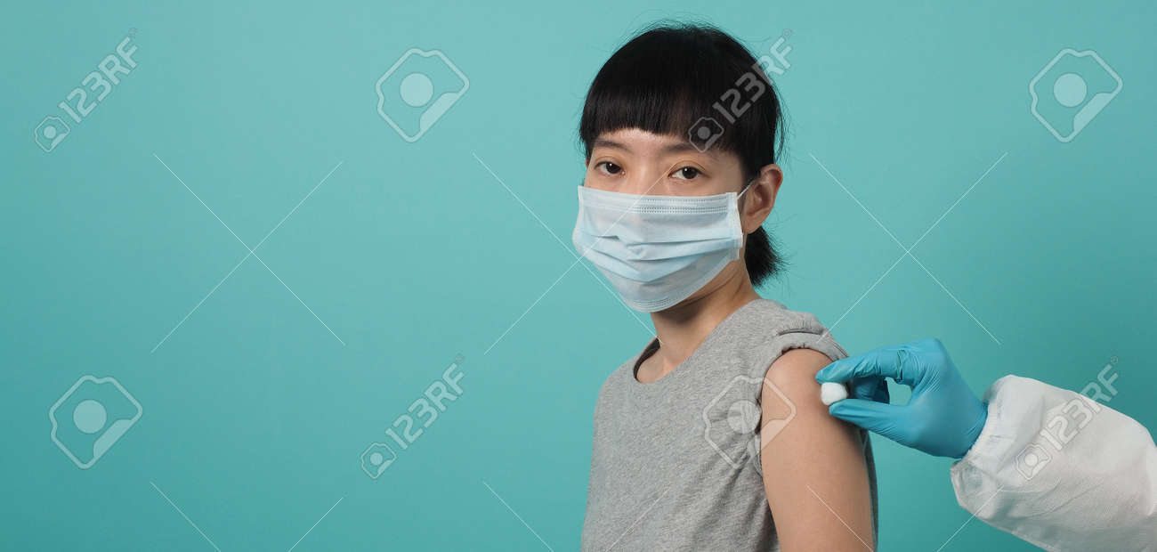 Vaccine Concept. Woman waiting for coronavirus vaccine injection by doctor. Asian woman with medical mask open shoulder and upper arm on blue green background. Waiting for vaccination. - 168300451