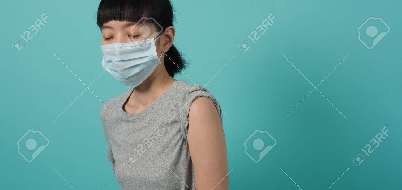 Vaccine Concept. Woman waiting for coronavirus vaccine injection by doctor. Asian woman with medical mask open shoulder and upper arm on blue green background. Waiting for vaccination. - 168300452