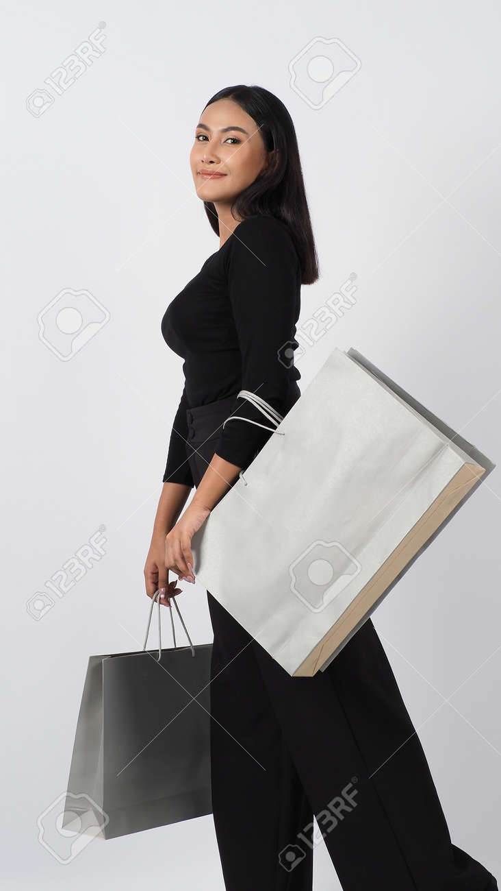 Love Shopping concept. Beautiful Asian woman carrying gray color bags shopping online. isolated on white studio background. online shopping bag. black hair woman love shopping online. Online purchase - 168300579