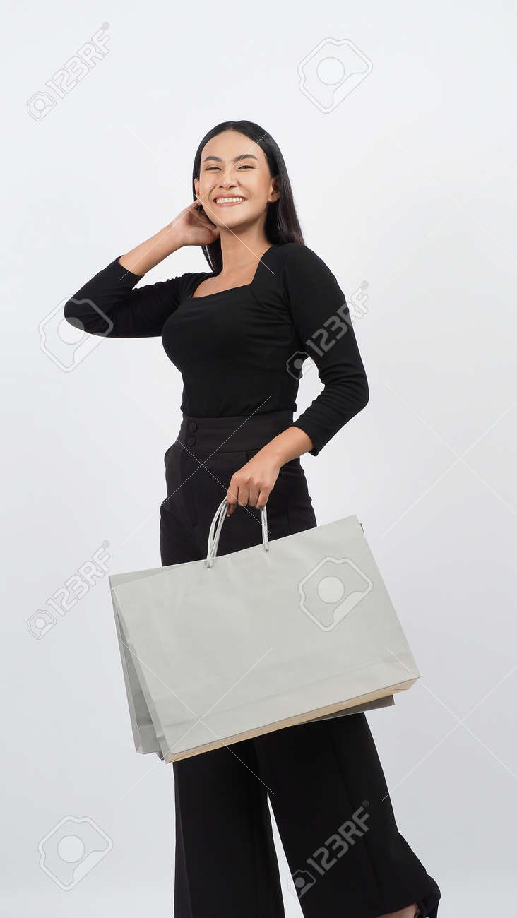Love Shopping concept. Beautiful Asian woman carrying gray color bags shopping online. isolated on white studio background. online shopping bag. black hair woman love shopping online. Online purchase - 168300583