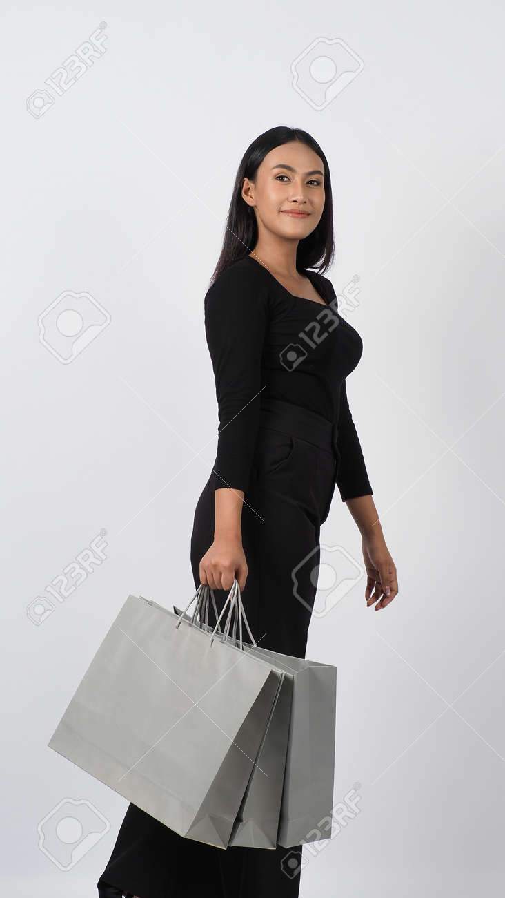 Love Shopping concept. Beautiful Asian woman carrying gray color bags shopping online. isolated on white studio background. online shopping bag. black hair woman love shopping online. Online purchase - 168300588