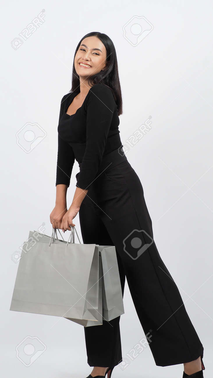 Love Shopping concept. Beautiful Asian woman carrying gray color bags shopping online. isolated on white studio background. online shopping bag. black hair woman love shopping online. Online purchase - 168300598
