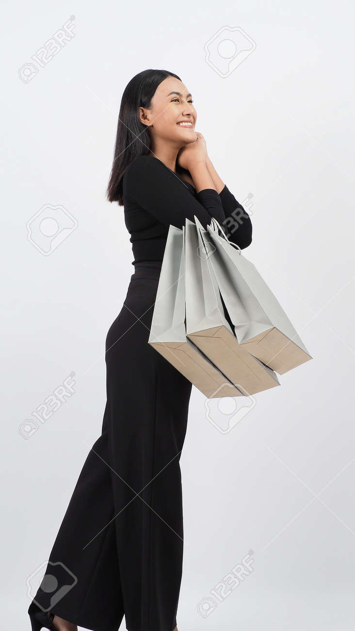Love Shopping concept. Beautiful Asian woman carrying gray color bags shopping online. isolated on white studio background. online shopping bag. black hair woman love shopping online. Online purchase - 168300603