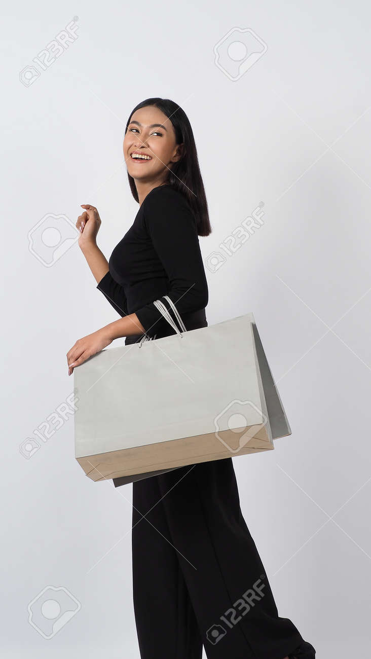 Love Shopping concept. Beautiful Asian woman carrying gray color bags shopping online. isolated on white studio background. online shopping bag. black hair woman love shopping online. Online purchase - 168300605