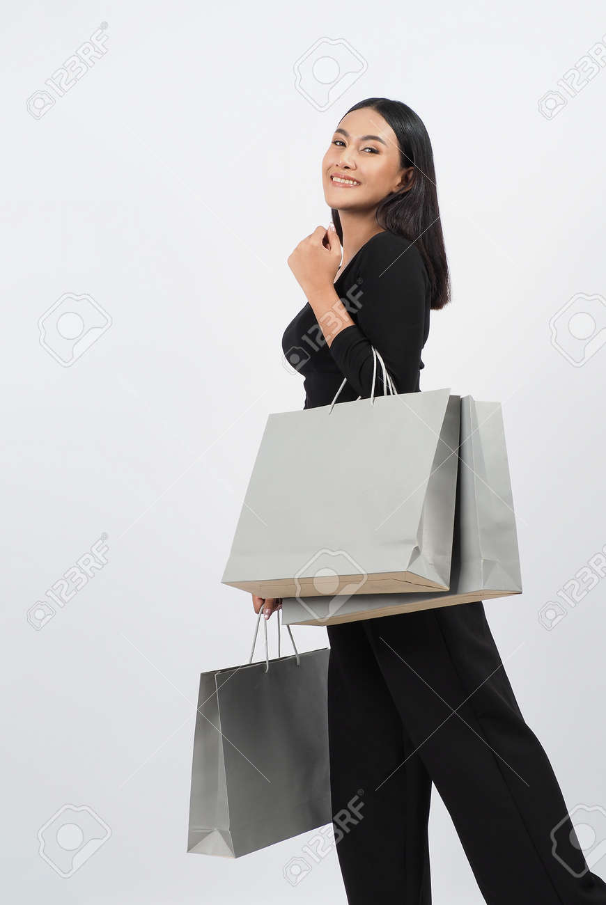 Love Shopping concept. Beautiful Asian woman carrying gray color bags shopping online. isolated on white studio background. online shopping bag. black hair woman love shopping online. Online purchase - 168301073