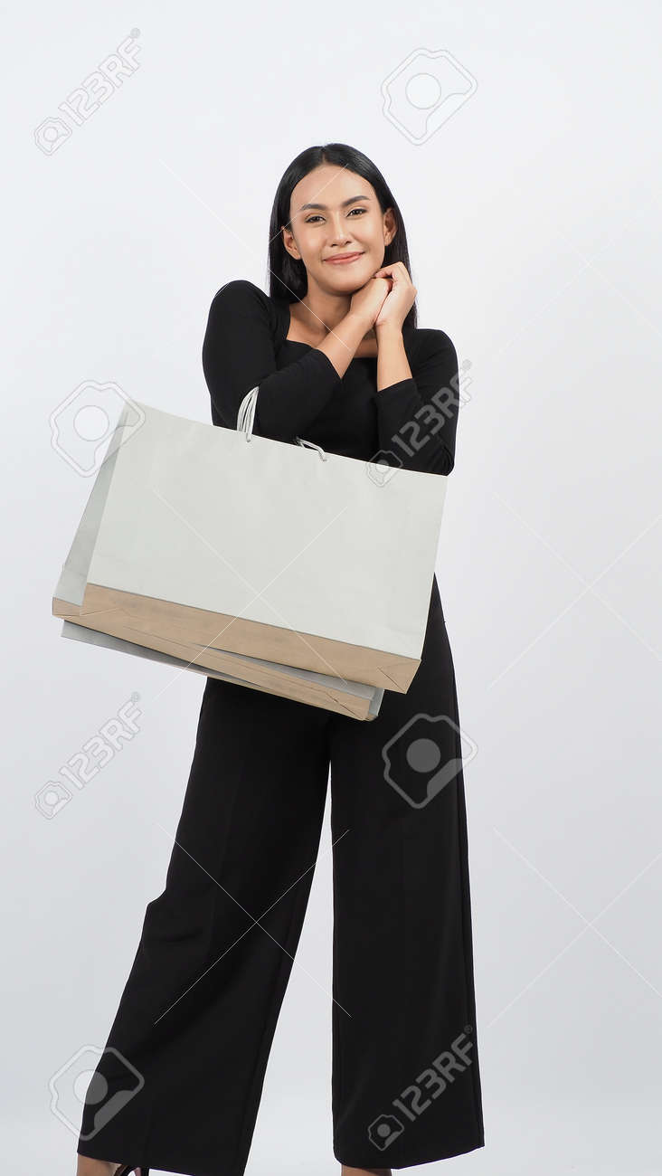 Love Shopping concept. Beautiful Asian woman carrying gray color bags shopping online. isolated on white studio background. online shopping bag. black hair woman love shopping online. Online purchase - 168301074
