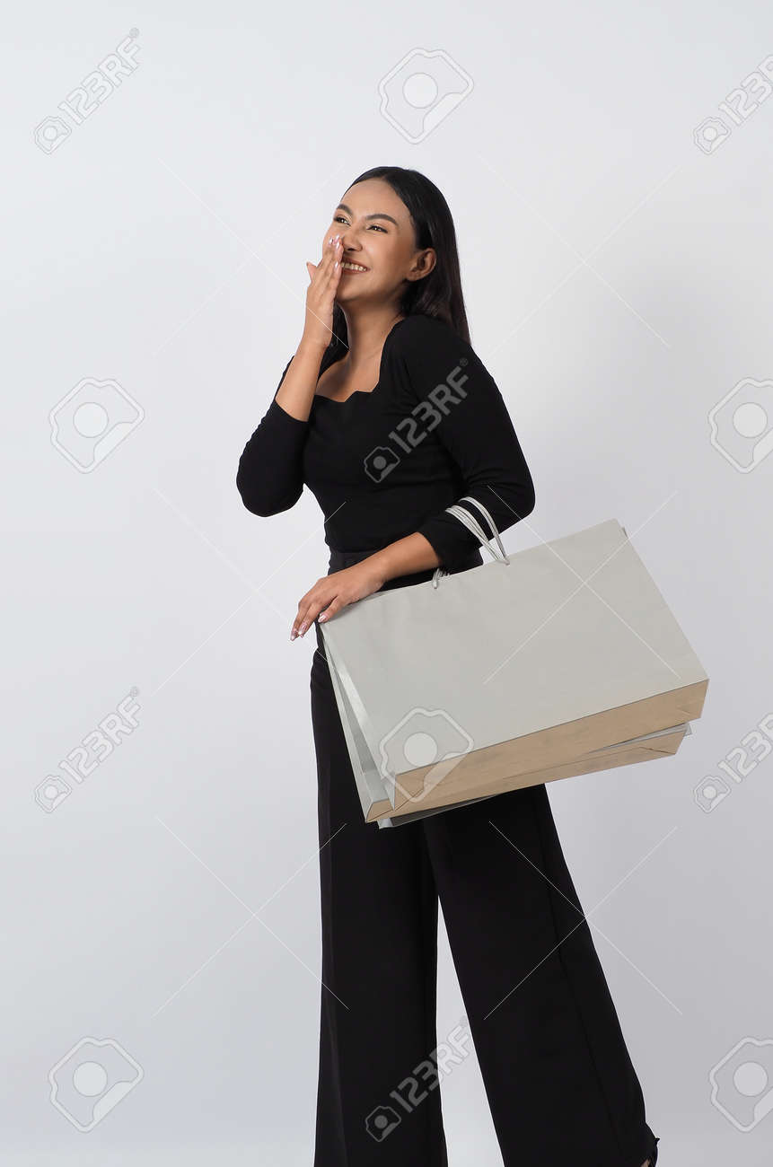 Love Shopping concept. Beautiful Asian woman carrying gray color bags shopping online. isolated on white studio background. online shopping bag. black hair woman love shopping online. Online purchase - 168301076