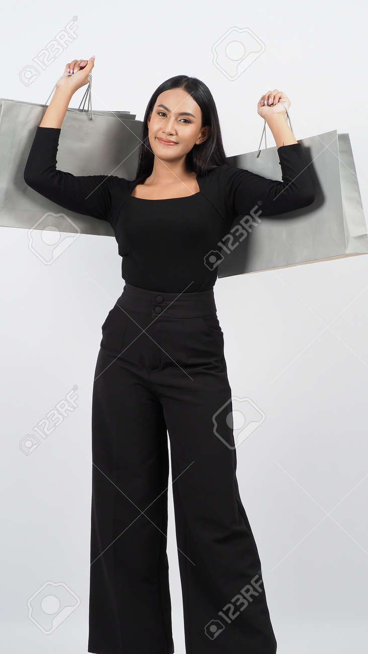 Love Shopping concept. Beautiful Asian woman carrying gray color bags shopping online. isolated on white studio background. online shopping bag. black hair woman love shopping online. Online purchase - 168301080
