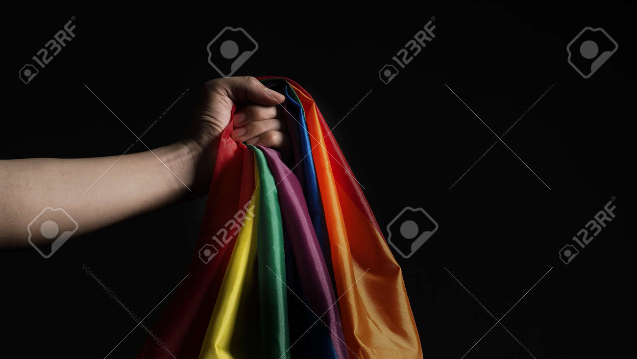 LGBTQ pride flag. Lesbian Gay Bi sexsual Transgender Queer. Homosexsual pride Rainbow flag in hand. black background. Represent symbol of freedom, peace, equality and love. LGBTQ concept. - 169136558