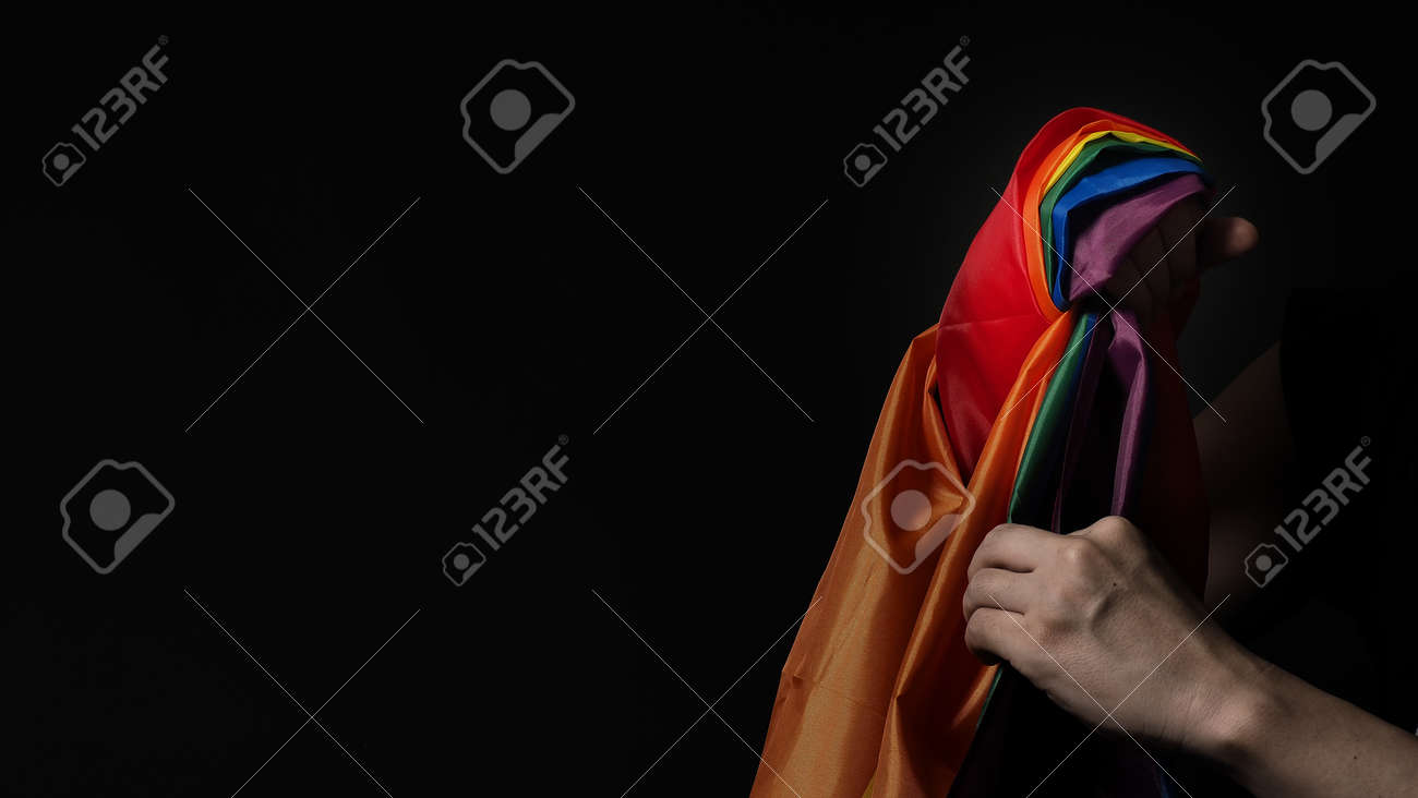 LGBTQ pride flag. Lesbian Gay Bi sexsual Transgender Queer. Homosexsual pride Rainbow flag in hand. black background. Represent symbol of freedom, peace, equality and love. LGBTQ concept. - 169136559