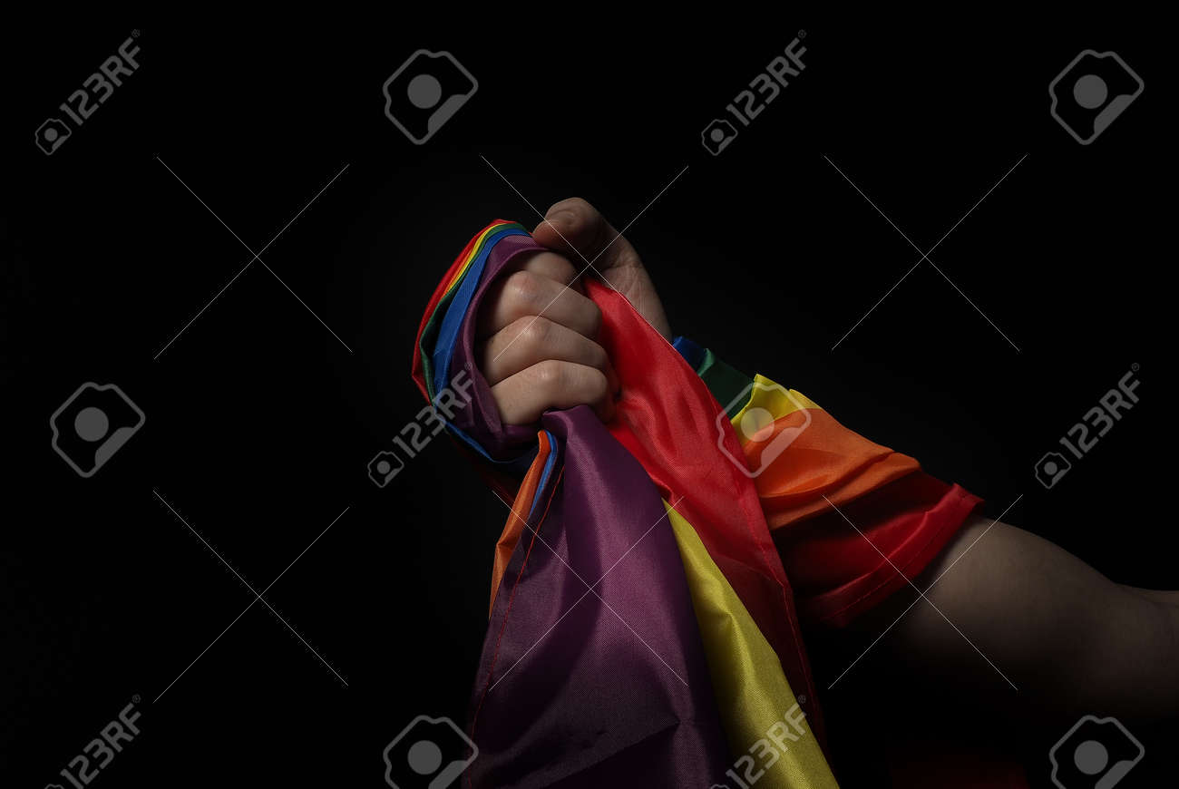 LGBTQ pride flag. Lesbian Gay Bi sexsual Transgender Queer. Homosexsual pride Rainbow flag in hand. black background. Represent symbol of freedom, peace, equality and love. LGBTQ concept. - 169136561