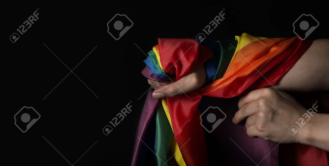 LGBTQ pride flag. Lesbian Gay Bi sexsual Transgender Queer. Homosexsual pride Rainbow flag in hand. black background. Represent symbol of freedom, peace, equality and love. LGBTQ concept. - 169136576