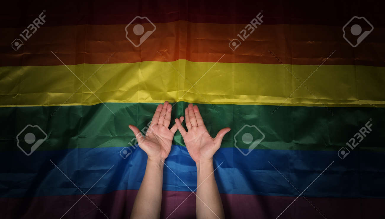 LGBTQ pride flag. Lesbian Gay Bi sexsual Transgender Queer. Homosexsual pride Rainbow flag in hand. black background. Represent symbol of freedom, peace, equality and love. LGBTQ concept. - 169136577