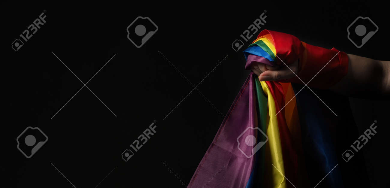 LGBTQ pride flag. Lesbian Gay Bi sexsual Transgender Queer. Homosexsual pride Rainbow flag in hand. black background. Represent symbol of freedom, peace, equality and love. LGBTQ concept. - 169136628