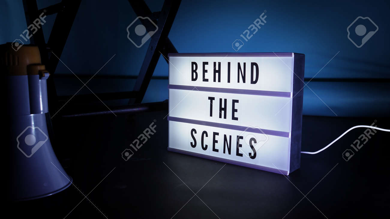 Behind the scenes letterboard text on Lightbox or Cinema Light box. Movie clapperboard megaphone and director chair beside. Background LED color change loop. static camera in video production studio. - 170416172