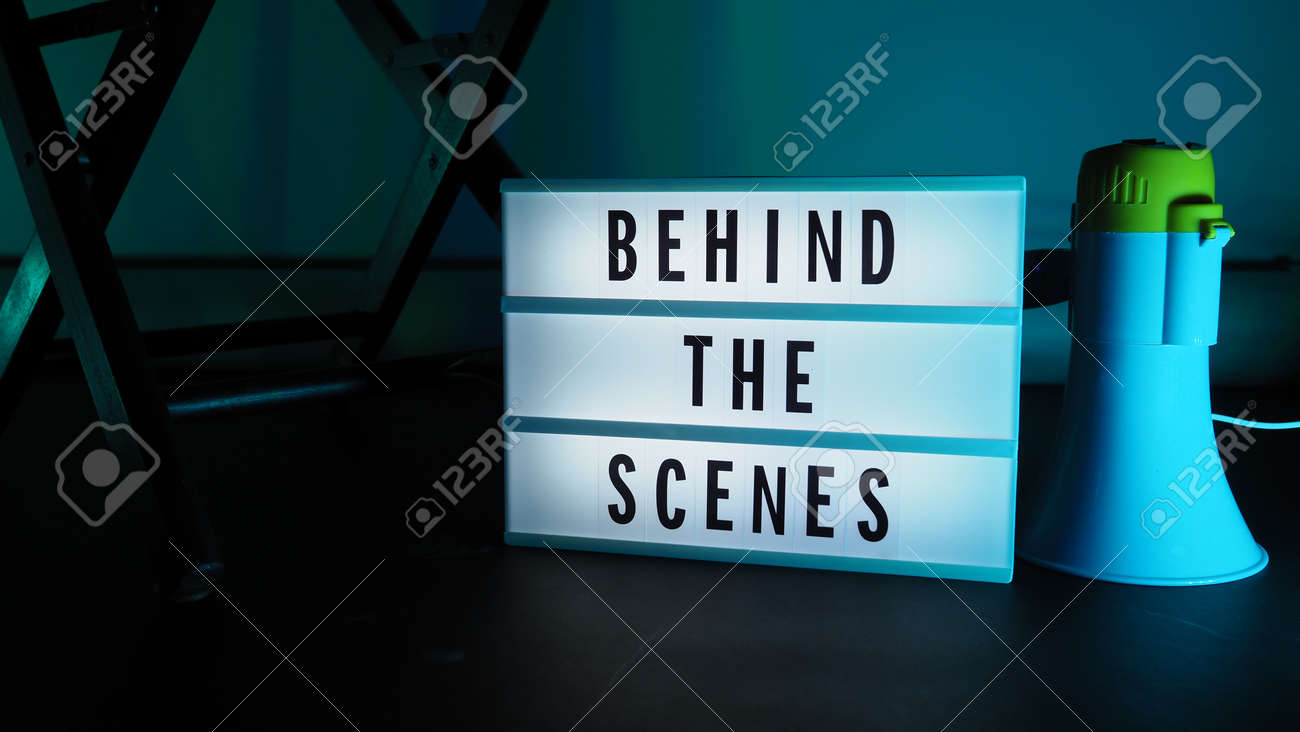 Behind the scenes letterboard text on Lightbox or Cinema Light box. Movie clapperboard megaphone and director chair beside. Background LED color change loop. static camera in video production studio. - 170416175