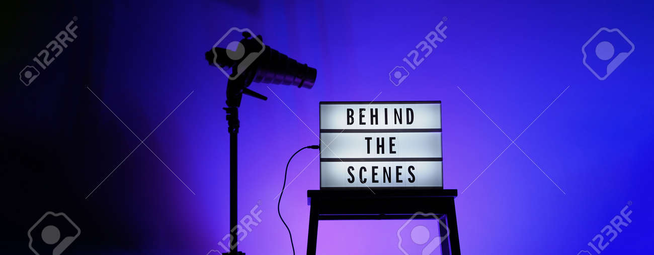 Behind the scenes letterboard text on Lightbox or Cinema Light box. Movie clapperboard megaphone and director chair beside. Background LED color change loop. static camera in video production studio. - 170416176