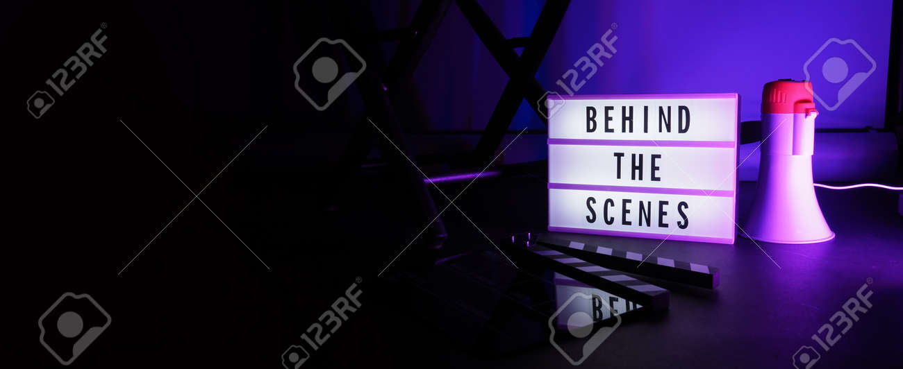 Behind the scenes letterboard text on Lightbox or Cinema Light box. Movie clapperboard megaphone and director chair beside. Background LED color change loop. static camera in video production studio. - 170416182