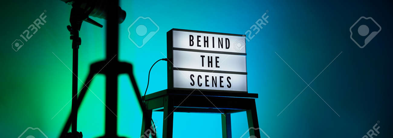 Behind the scenes letterboard text on Lightbox or Cinema Light box. Movie clapperboard megaphone and director chair beside. Background LED color change loop. static camera in video production studio. - 170416183