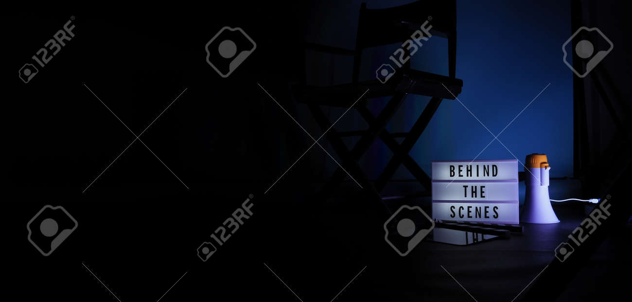 Behind the scenes letterboard text on Lightbox or Cinema Light box. Movie clapperboard megaphone and director chair beside. Background LED color change loop. static camera in video production studio. - 170416184