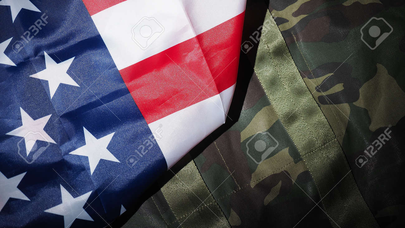 Military hat or bag laying with american flag. Soldier hat or helmet with national american flag on black background. Represent military concept by camouflage object and USA nation flag. - 170416250