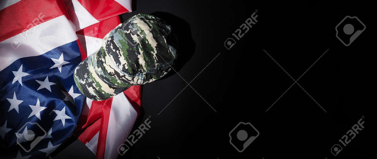 Military hat or bag laying with american flag. Soldier hat or helmet with national american flag on black background. Represent military concept by camouflage object and USA nation flag. - 170416251