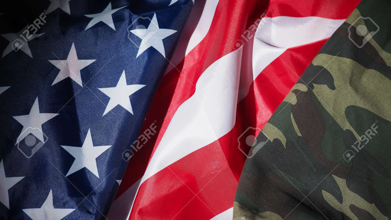 Military hat or bag laying with american flag. Soldier hat or helmet with national american flag on black background. Represent military concept by camouflage object and USA nation flag. - 170416253