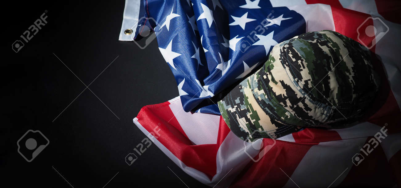 Military hat or bag laying with american flag. Soldier hat or helmet with national american flag on black background. Represent military concept by camouflage object and USA nation flag. - 170416256