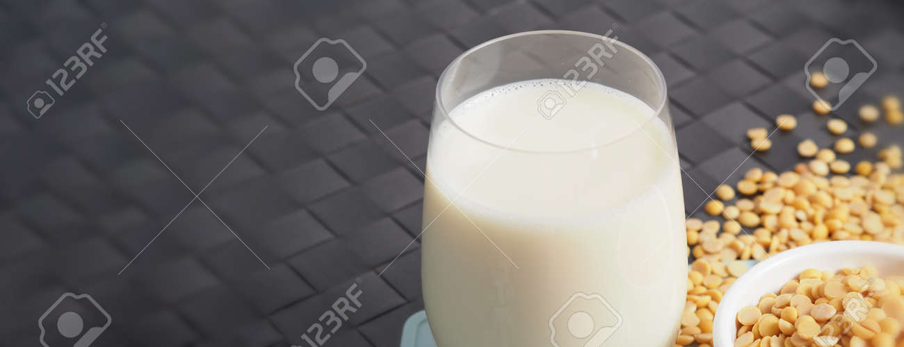 Soy milk with no sugar added in a glass on a green color plastic plate mat. Close-up images of home made healthy soy milk drink and soy beans in small bowl. Black background in a studio shot. Soymilk. - 171186416