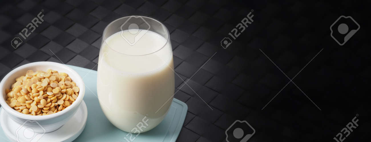Soy milk with no sugar added in a glass on a green color plastic plate mat. Close-up images of home made healthy soy milk drink and soy beans in small bowl. Black background in a studio shot. Soymilk. - 171186459