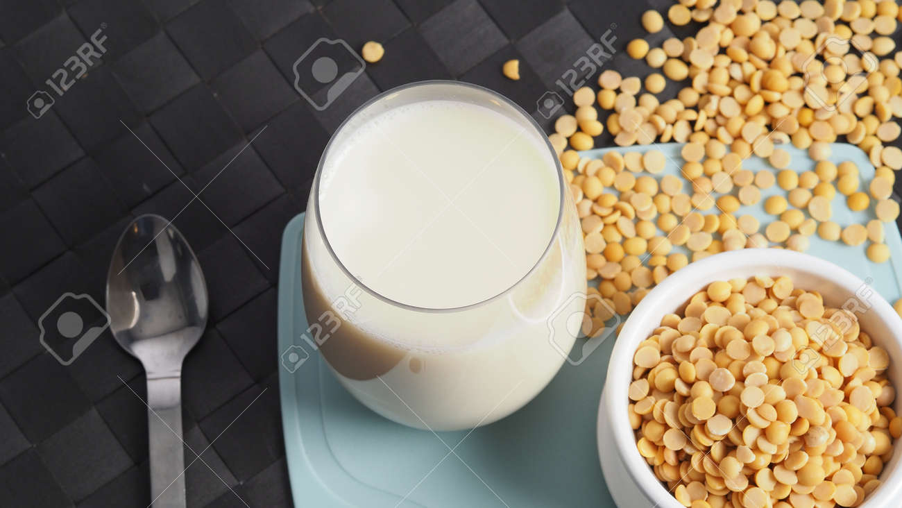 Soy milk with no sugar added in a glass on a green color plastic plate mat. Close-up images of home made healthy soy milk drink and soy beans in small bowl. Black background in a studio shot. Soymilk. - 171186562