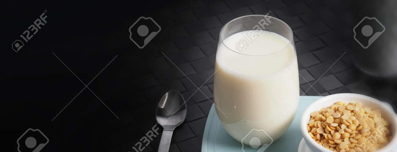 Soy milk with no sugar added in a glass on a green color plastic plate mat. Close-up images of home made healthy soy milk drink and soy beans in small bowl. Black background in a studio shot. Soymilk. - 171186518