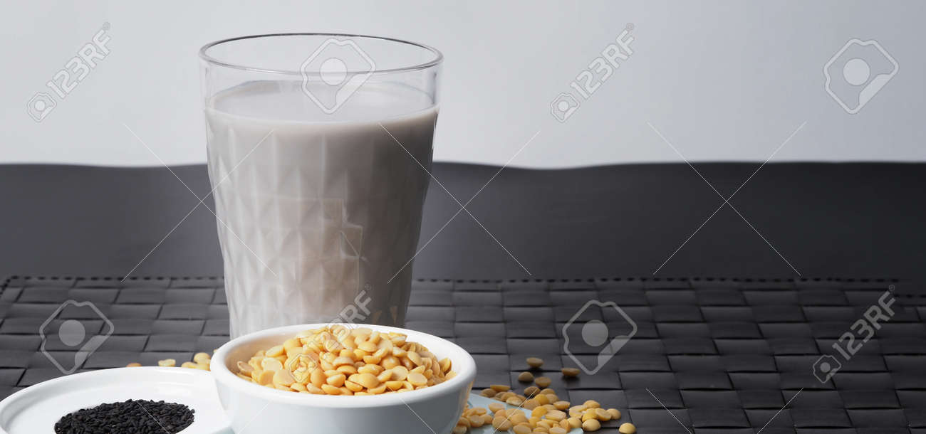 Soy milk blended with black sesame in clear glass on black plate mat. Black sesame seed and soy beans in a cup. Black sesame soy bean blended milk. Healthy drink with natural ingrediant. Soya milk. - 171239771