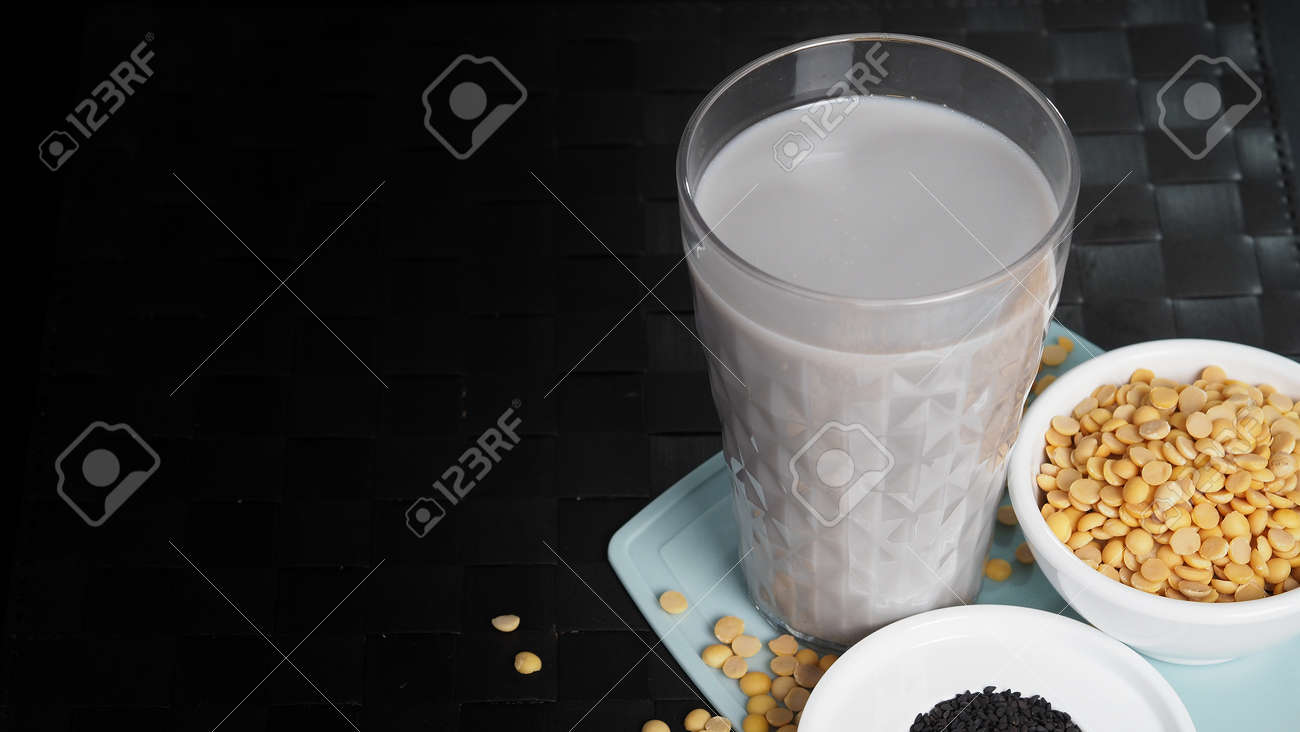 Soy milk blended with black sesame in clear glass on black plate mat. Black sesame seed and soy beans in a cup. Black sesame soy bean blended milk. Healthy drink with natural ingrediant. Soya milk. - 171239774