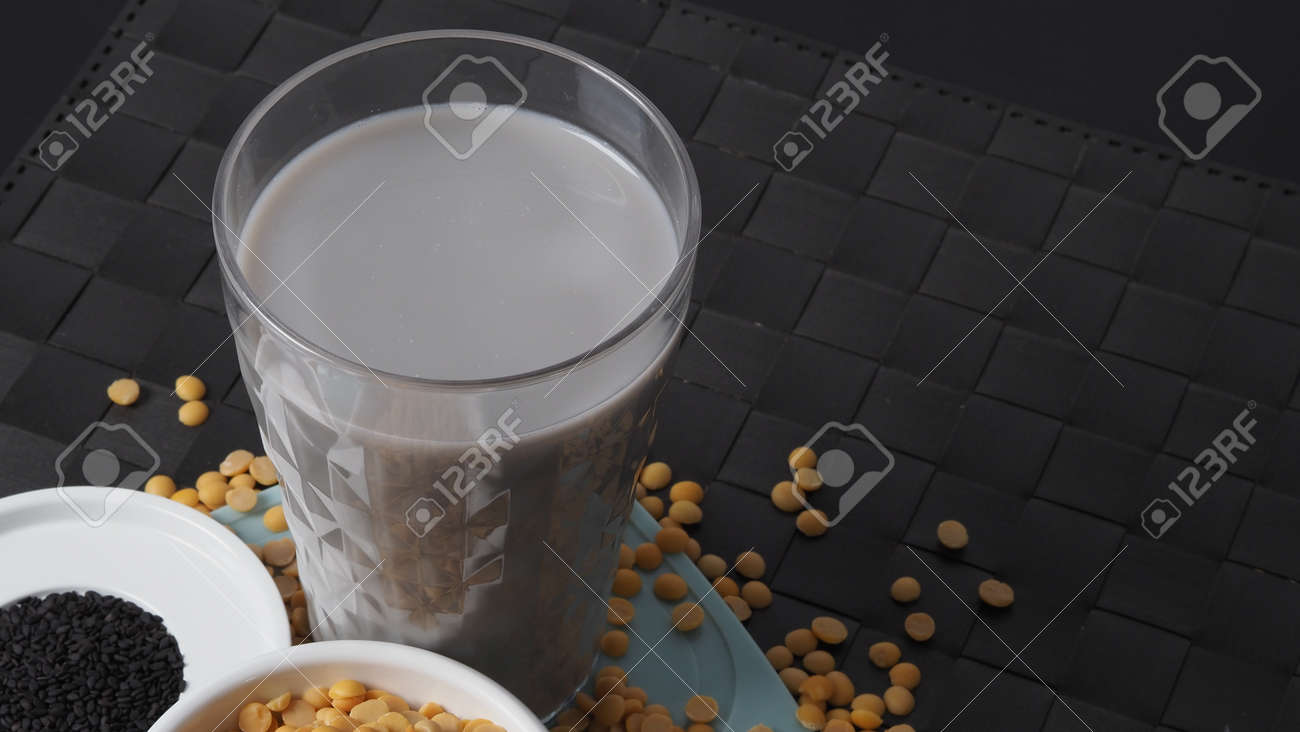 Soy milk blended with black sesame in clear glass on black plate mat. Black sesame seed and soy beans in a cup. Black sesame soy bean blended milk. Healthy drink with natural ingrediant. Soya milk. - 171239776