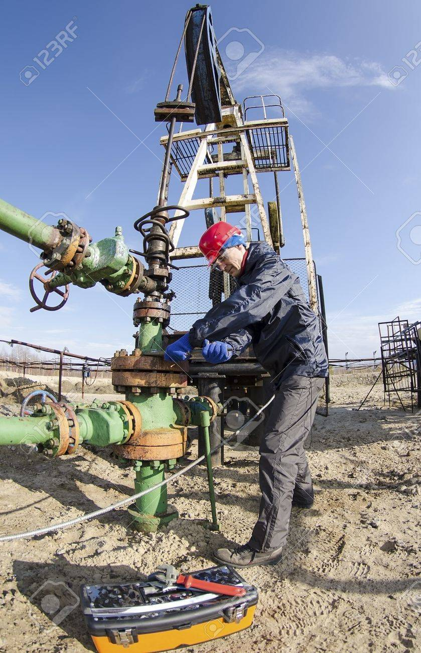 Worker reparing wellhead with the wrench in the oilfield  Tool