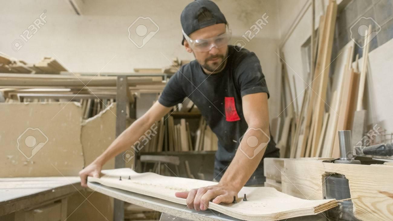 Young artisan man cutting longboard deck - 56219641