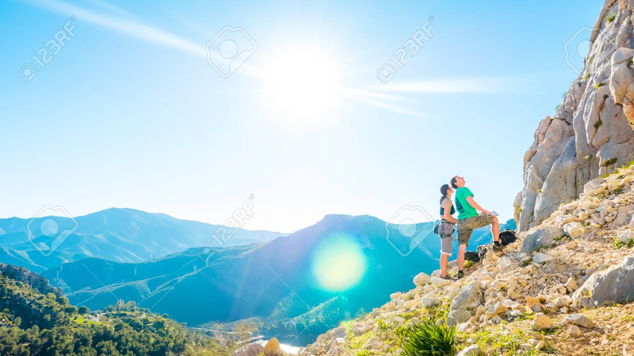 Young adult caucasian couple examining the mountain wall to climb - 58641229