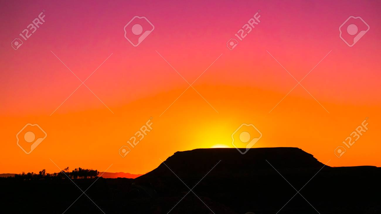 Sun slowly fading behind the mountain in the distance - 58641320
