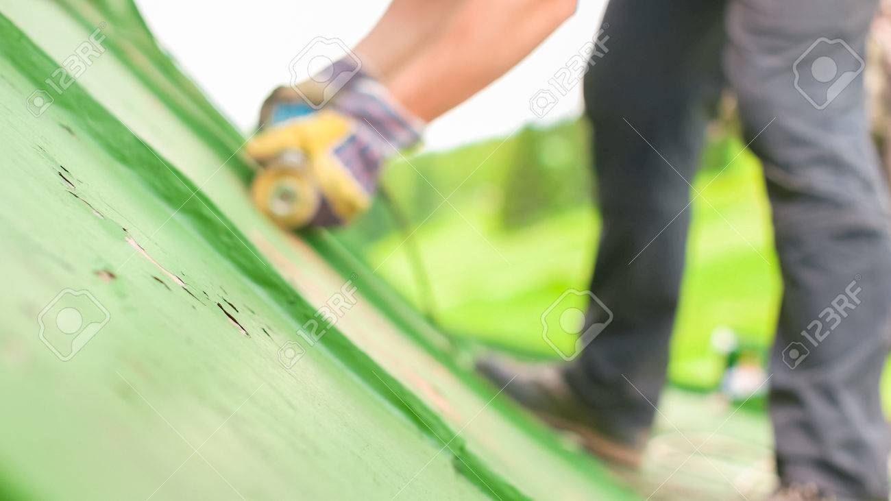Construction worker using tools to scrape off green paint - 60155419