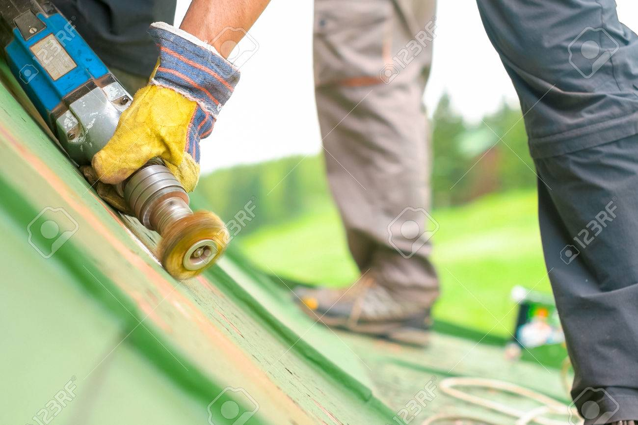 Construction worker using tools to scrape off green paint, low angled - 60155597