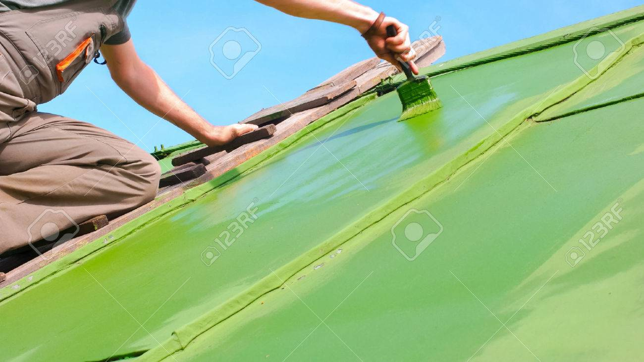 Adult caucasian man aplying second layer of paint to the roof - 60176898